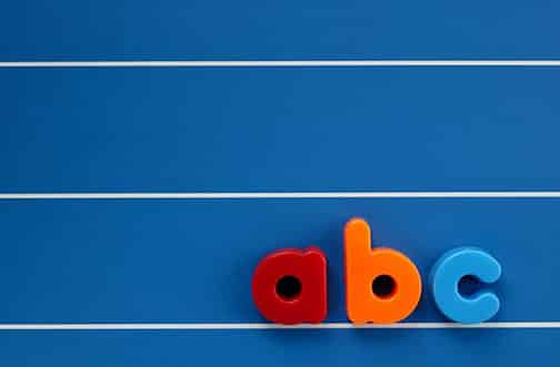 The letters a, b and c from a child's toy alphabet set, placed on a blue, lined background. Space for text elsewhere in the image.