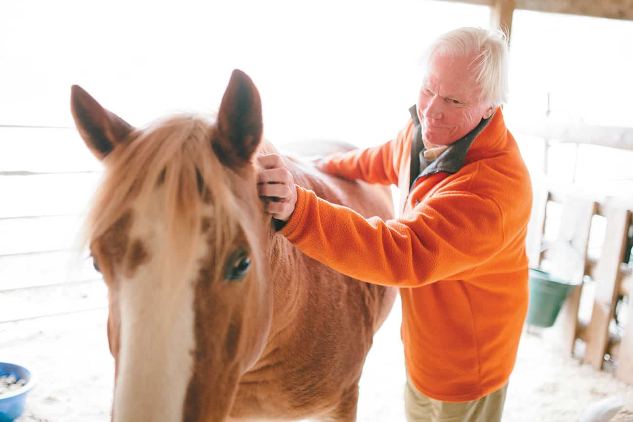 Spending time with the animals on his farm – home to cattle, hogs, goats, geese, ducks, chickens and Elmer here – helps Dr. Jim Dykes relax and rejuvenate.