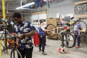 Robert Weston, volunteer Ronnie Rozenkranz-Boxford and Rob Walpole, the co-op's construction coordinator, repair bikes at the Durham Bike Co-Op.