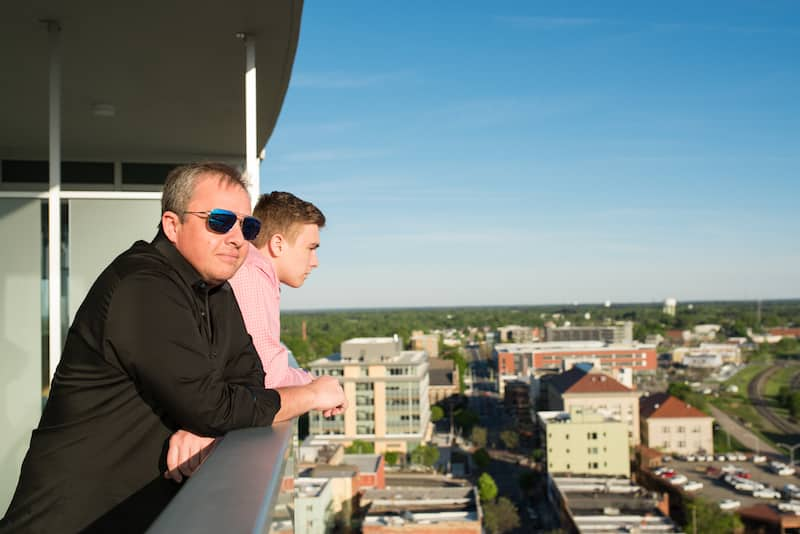 Gray Ellis and his son, Nik, take in the afternoon sun on their 15th-floor balcony at One City Center.