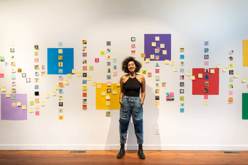 Saba Taj stands in front of several works in the 'Sticky Note Show' at The Carrack.