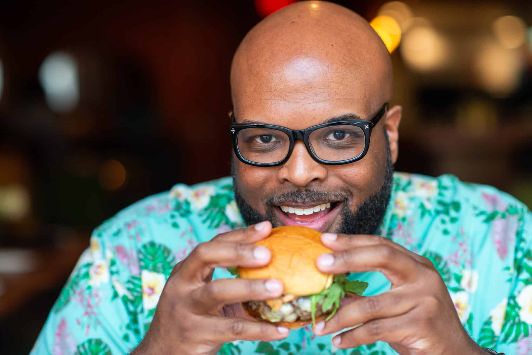 Amos Cooper Jr. eating a burger at Alley Twenty Six