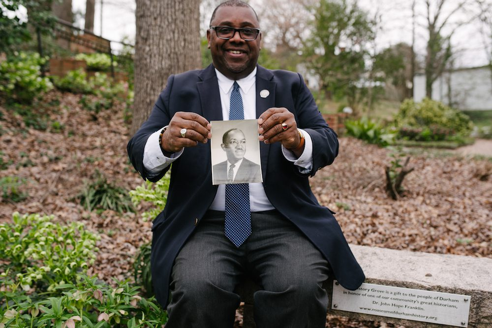 Andre Vann holding a photo of Dr. John Hope Franklin at a History Groves site
