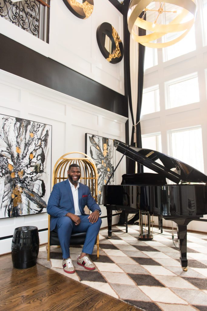 Don Ricardo Massenburg sits in one of his interior design projects with modern art and a black grand piano.