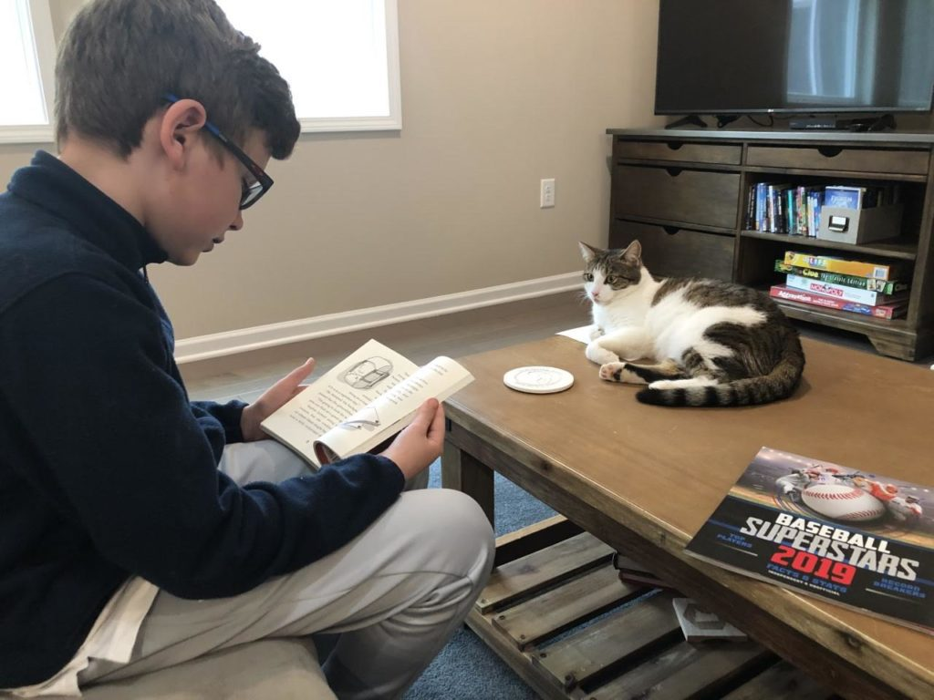 Third grader Brady Gentile reads to his cat during the COVID-19 quarantine
