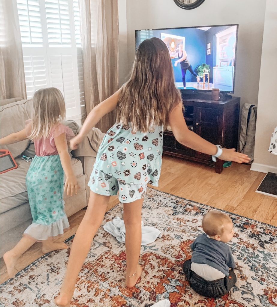 Christi Mackey's kids, Reese Mackey, 8, Rowen Mackey, 4, and Riggs Mackey, 7 months, have made the switch to taking yoga class from their home living room during the COVID-19 quarantine
