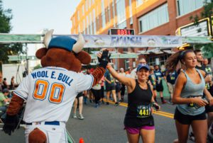 At the Bull Moon Ride and Run's finish line a runner high-fives Wool E. Bull with a giant smile on her face.