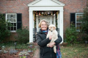 Kelly Witter holding her dog in front of her home in Trinity Park