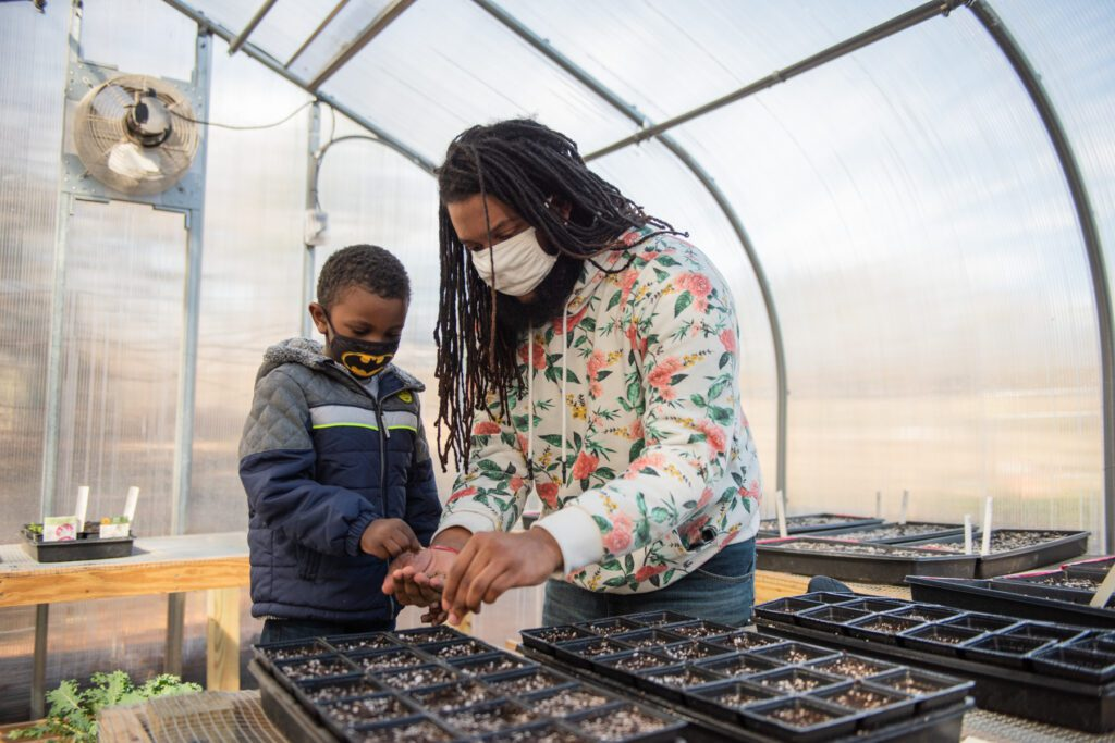 T'Challa Smith and Derek Haynes plant sweet pepper seeds in the greenhouse at Briggs Avenue Community Garden.