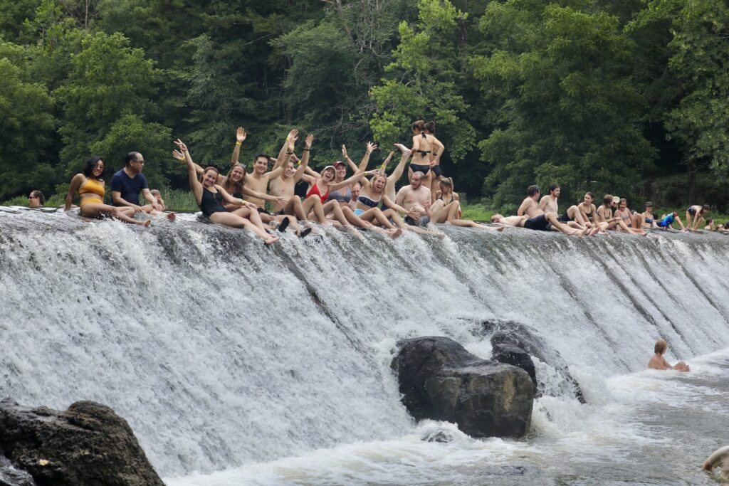 Crowd of people in bathing suits sitting on the rocks at the Eno River